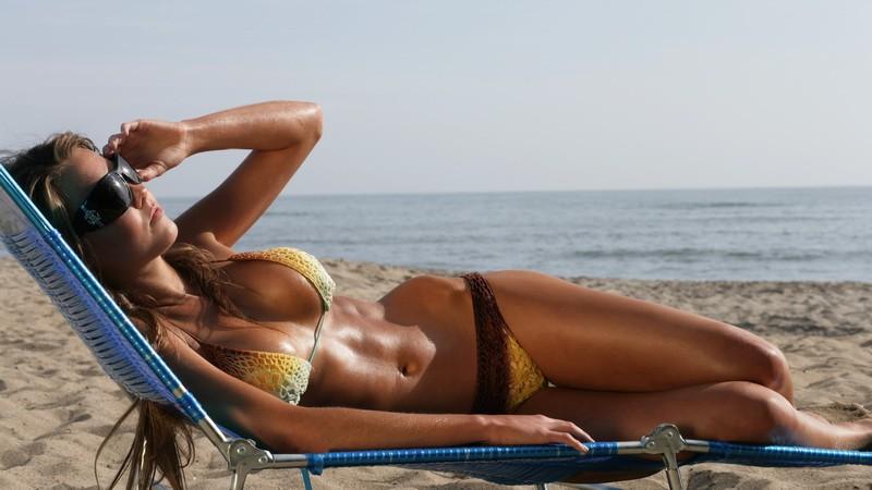 Žena na pláži_na lehátku_ilustračná foto_leto