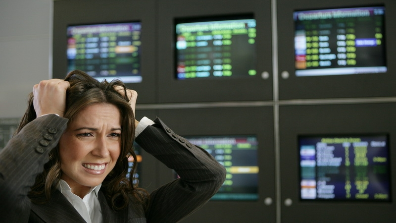 Žena v strese na burze, za ňou počítače