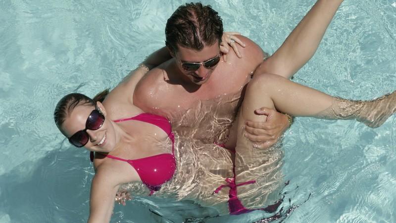 Muž drží ženu v rukách, bazén, Chorvátsko