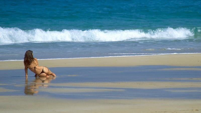 žena na pláži v bikinách, more za ňou