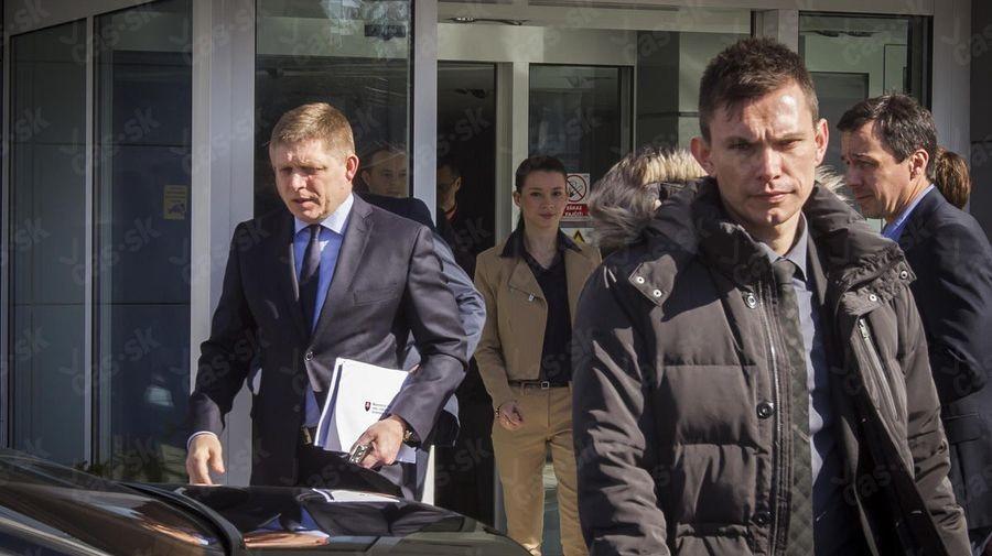 Premiér Robert Fico, v pozadí jeho asistentka Mária Trošková.